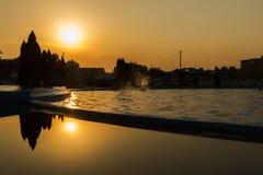 在池日落游泳 免版税库存图片