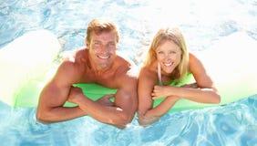 在池松弛游泳之外的夫妇 免版税库存照片