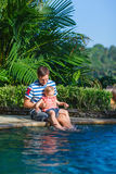 在池游泳附近的女儿父亲 库存图片