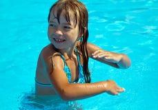 在池的愉快的女孩跳舞 免版税库存照片