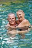 在池的愉快的高级夫妇 库存照片
