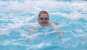 在池的男孩游泳 免版税图库摄影