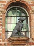 在污迹玻璃窗前面的狗雕象 库存照片