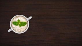 在汤碗的未加工的米在与薄荷的叶子的木台式 免版税图库摄影