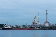在汽油精炼厂背景的油箱船 免版税库存照片