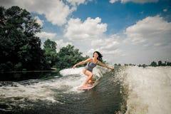 在汽艇波浪的深色的妇女骑马wakeboard  库存照片