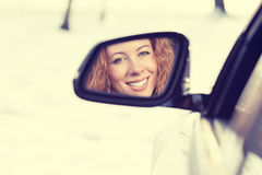 在汽车侧视图镜子的愉快的妇女司机反射 安全冬天旅行,驾驶概念的旅途 免版税图库摄影