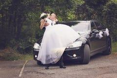 在汽车前的可爱的婚礼夫妇 图库摄影