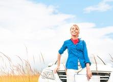 在汽车前面的旅游妇女在夏天域。 免版税库存图片