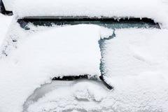 在汽车后视镜的雪 结冰的汽车,白色汽车盖了雪冬日 城市生活都市场面在冬天 免版税库存照片