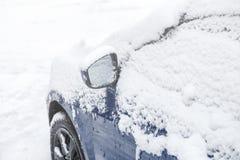 在汽车后视镜的雪 结冰的汽车,蓝色汽车盖了雪冬日 城市生活都市场面在冬天 库存图片