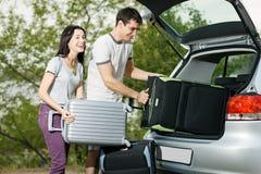 在汽车启动的新夫妇装载手提箱 免版税图库摄影