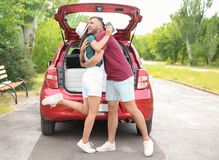 在汽车和手提箱附近的美好的夫妇为在树干的夏天旅途包装了 免版税库存图片