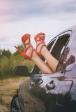 在汽车外面的妇女的腿 免版税图库摄影