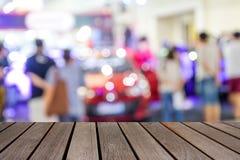 在汽车展示会展示室马达商展的被弄脏的图象木桌为 免版税库存照片