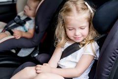 在汽车座位的小孩逗人喜爱的孩子 免版税库存照片