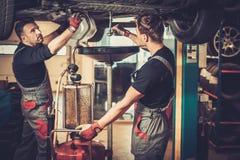 在汽车引擎的汽车修理师改变的机油在维护修理服务站在汽车车间 图库摄影