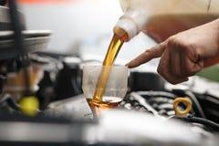 在汽车引擎的Profecional汽车修理师改变的机油在维护修理服务站在汽车车间 免版税库存照片