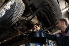 在汽车引擎的Profecional汽车修理师改变的机油在维护修理服务站在汽车车间 库存照片