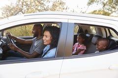 在汽车微笑的年轻黑家庭在旅行 库存图片