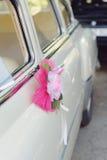 在汽车把柄的桃红色花 免版税图库摄影