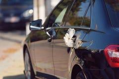 在汽车把柄的桃红色花 免版税库存图片