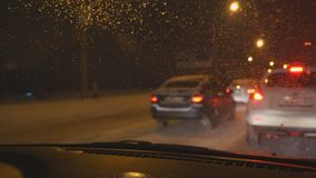 在汽车挡风玻璃的下落在晚上 夜交通在城市在冬天 影视素材