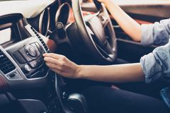 在汽车收音机的亚洲妇女按钮听的到音乐 图库摄影