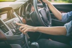 在汽车收音机的亚洲妇女按钮听的到音乐 免版税库存照片