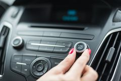 在汽车收音机的妇女改变的频率 免版税库存照片