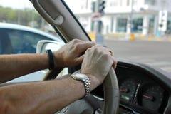 在汽车方向盘的手 免版税图库摄影