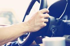 在汽车方向盘的手  免版税库存图片