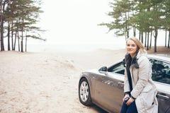 在汽车旁边的愉快的妇女,放松在旅行冒险旅行 免版税库存照片