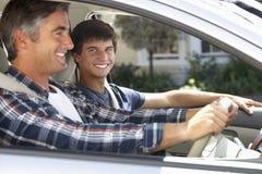 在汽车旅途上的父亲与十几岁的儿子 库存图片