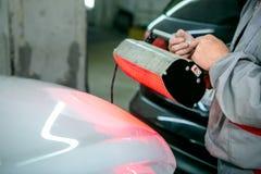 在汽车服务的汽车修理 绘工作 锁匠烘干被绘的汽车细节,特写镜头 免版税库存照片