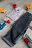 在汽车玩具附近的男孩成套装备 镶边衬衣、牛仔布裤子和蓝色小船穿上鞋子黄色红色汽车 回到视图 免版税图库摄影