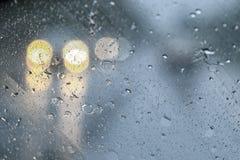 在汽车玻璃背景的雨下落 免版税库存图片