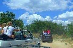 在汽车的儿童乘驾在土路 免版税库存图片