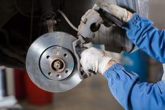 在汽车的全新的闸圆盘在车库 汽车机械师修理 免版税库存照片