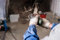 在汽车的全新的闸圆盘在车库 汽车机械师修理 库存照片