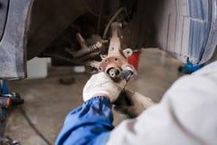 在汽车的全新的闸圆盘在车库 汽车机械师修理 库存图片