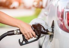在汽车的妇女抽的汽油燃料在加油站 库存照片