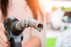 在汽车的妇女抽的汽油燃料在加油站 免版税图库摄影