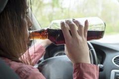 在汽车的妇女饮用的酒精 免版税库存图片