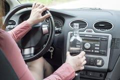 在汽车的妇女饮用的酒精 图库摄影