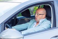 在汽车的害怕的滑稽的看起来的年轻人司机 无经验 免版税图库摄影