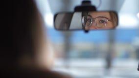 在汽车的射击,反映在前面镜子 与玻璃的美丽的女性眼睛在4K缓慢的Mo附近看 股票录像