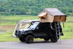 在汽车的屋顶的帐篷有露营地和草坪的在有美好的绿色自然风景的停车场附近 免版税库存图片