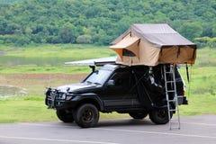 在汽车的屋顶的帐篷有露营地和草坪的在有美好的绿色自然风景的停车场附近 免版税图库摄影