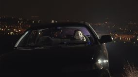 在汽车的幼小母司机在晚上,在城市背景点燃 股票录像
